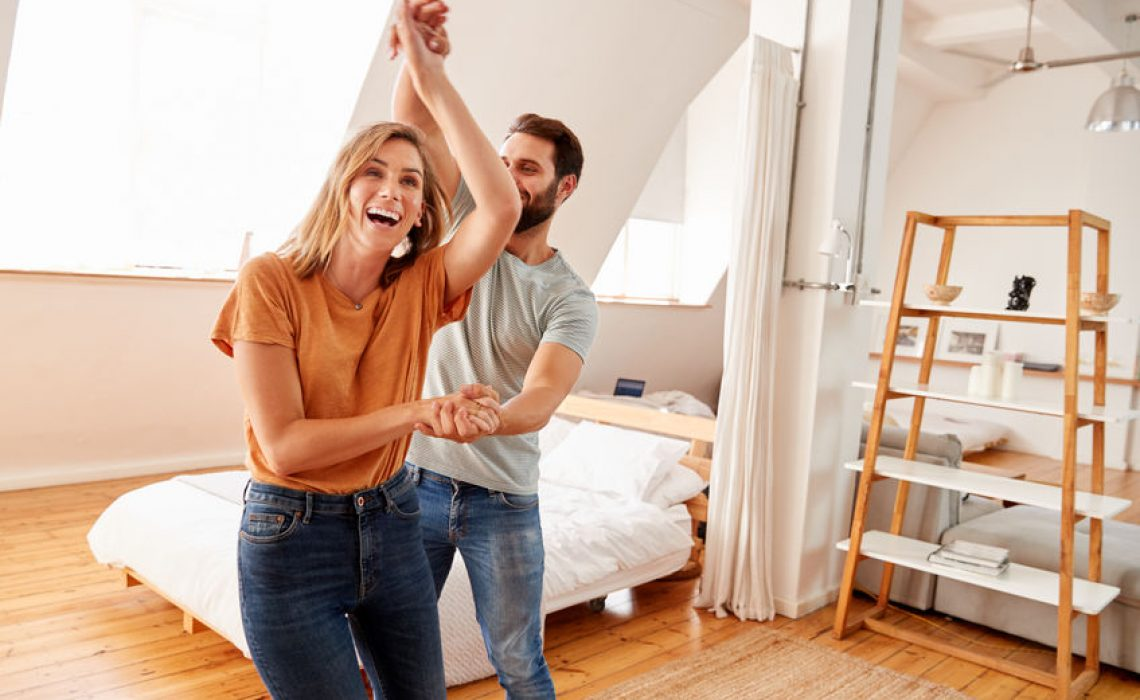 Couple Having Fun In New Home Dancing Together